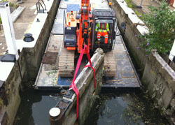 Old lock mitre gates being lifted out at Thames Weir Lock, Brentford, London on the Grand Union Canal.